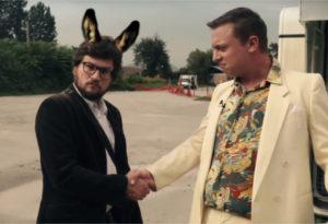Fotografija komika Igorja Bračiča z oslovskimi ušesami in poslovneža med rokovanjem