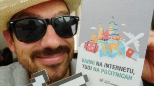 Naslovna slika videa, na kateri je Jože s sončnimi očali in poletnim klobukom, v rokah pa drži priročnik Varni na počitnicah