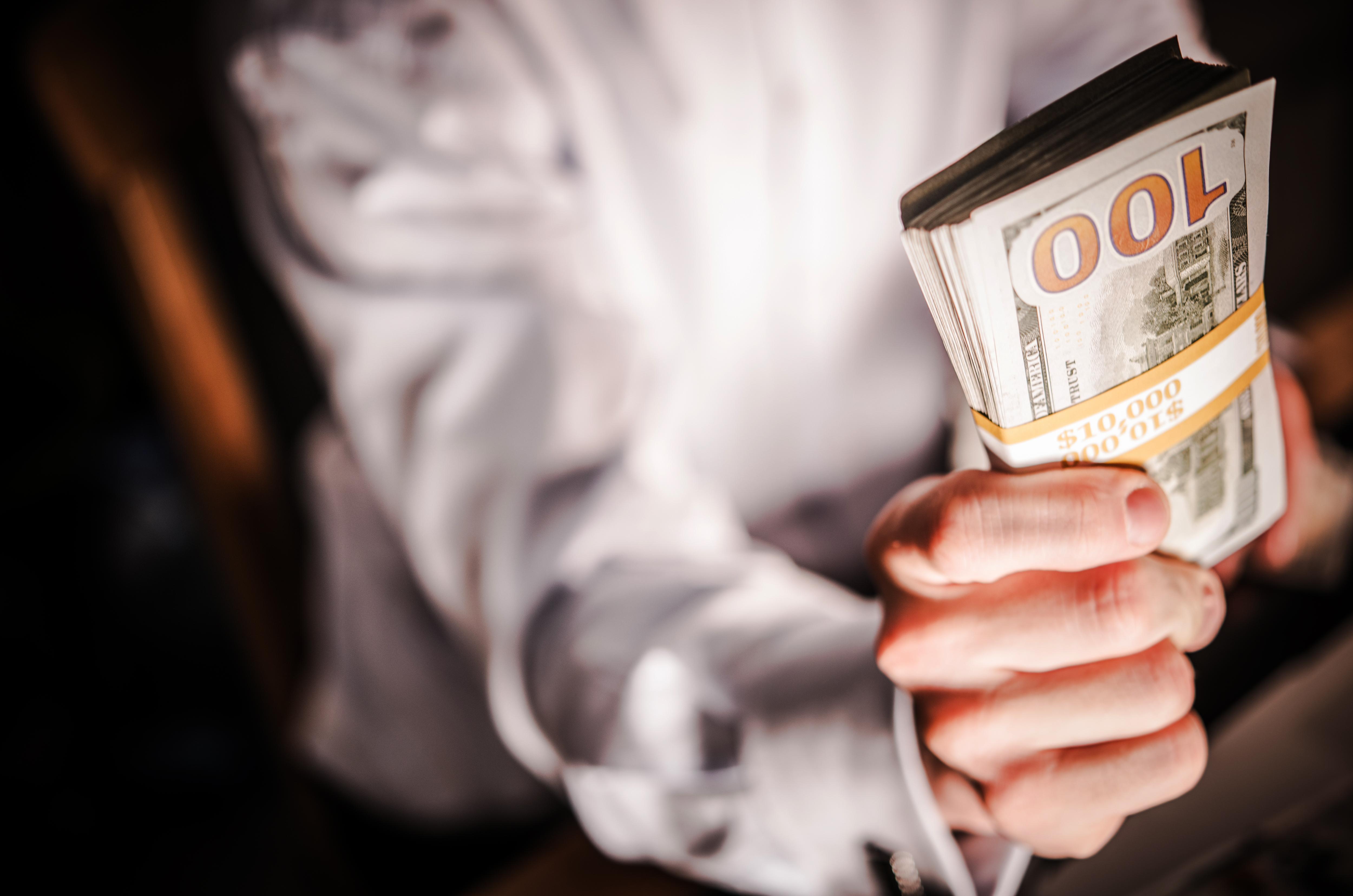 Fotografija moškega, ki v rokah drži šop bankovcev